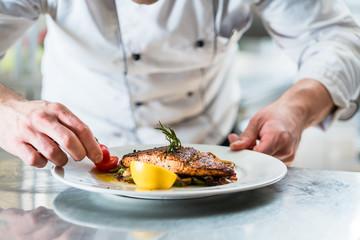 Koch mit Sorgfalt beim Garnieren eines Gerichts, Fisch mit Gemüse