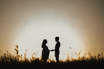 Silhouette portrait of beautiful young anonymous pregnant family in expectation of baby. Man and woman standing face to face over sunset sky background in evening in scenic nature landscape background