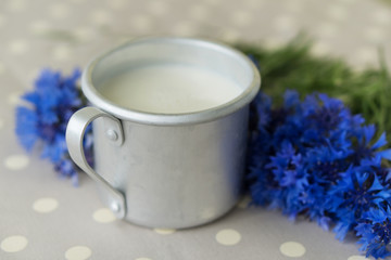 Mug of milk and cornflowers on a vintage tablecloth. Close-up.