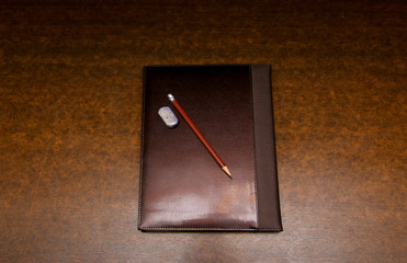 Brown Leather notebooks with pencil on white wooden background
