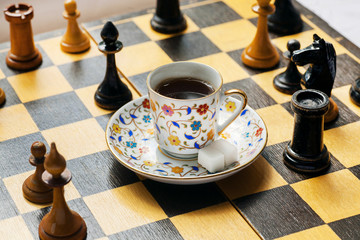 Tactic and strategy of modern life in concept. Cup of coffee on chessboard