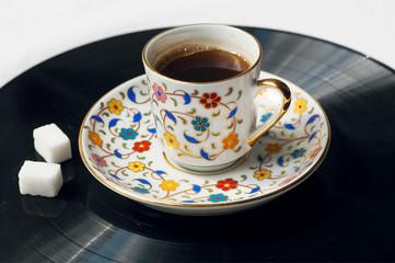 Cup of black coffee on surface of music vinil plate. Sound of morning.