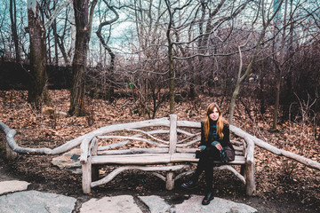 Girl sitting on a bench at the Central Park in Manhattan, New Yo