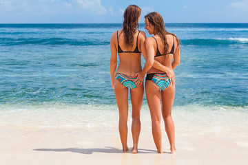Two beautiful adult girls in bikini have a fun and walk by white sand beach along sea surf. Active lifestyle, people outdoor activity on summer vacation on tropic island.