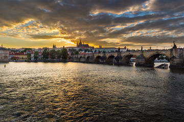 Cityscape of Prague with Castle and Charles Bridge at dramatic sunset, Czech Republic