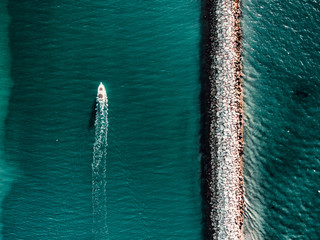 Boat passing by sea wall, view from above