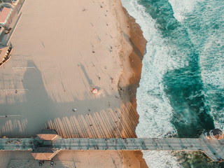 Overhead view of pier and ocean with sandy beach