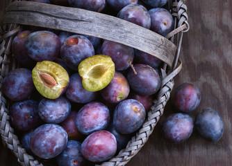 Fresh ripe black plums in a basket