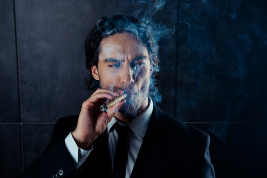 Closeup portrait of brutal young man  smoking a cigar