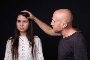 Domestic violence - man holding hand on woman's head, she is looking scared, dark background