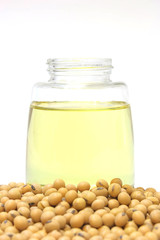 Soybean seed with oil in glass bottle setup isolated on  a white background,closeup