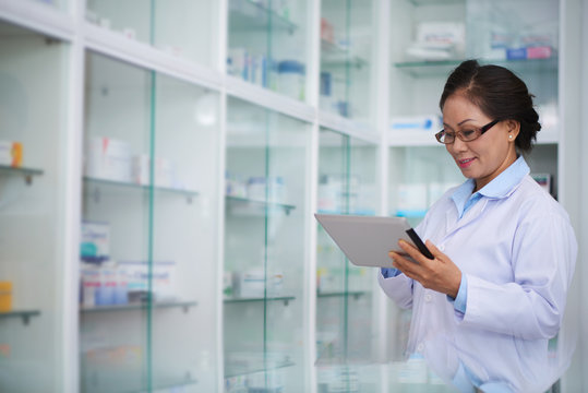 Female pharmacist with digital tablet searching for medication
