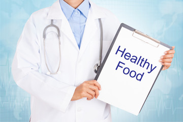 Doctor holding clipboard with healthy food text on a sheet of paper. on white background