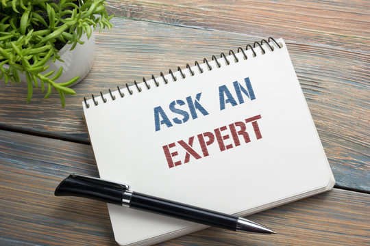 Ask an expert. Notepad with message, pen, reminder and flower. Office supplies on desk table top view.
