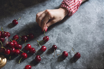 Woman's Hand Picking Fresh Cherries from a Concrete Table