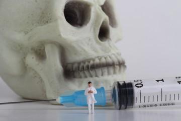 miniatura di medico con siringa e teschio