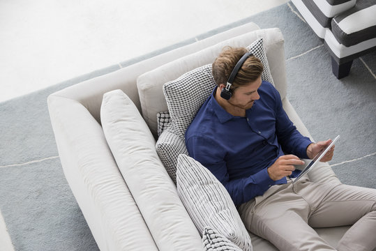 Young man sitting on couch using a digital tablet