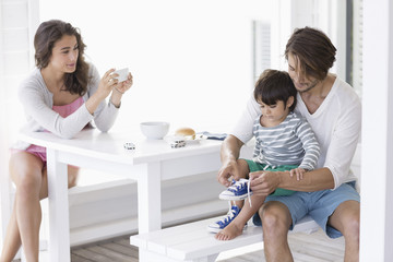 Woman taking picture of husband and son with mobile camera at home