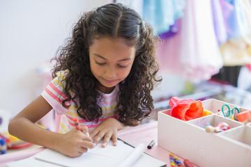 Little girl doing homework on table