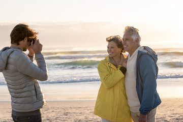 Young man taking a picture of his parents with camera on the beach