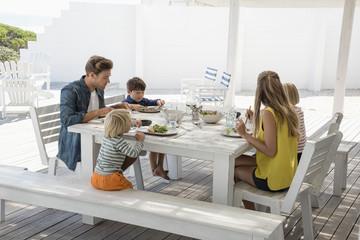 Young family enjoying food at porch