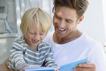 Happy father and son reading a book