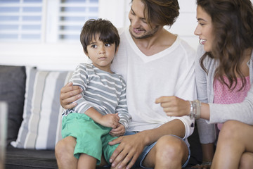 Happy family sitting on couch in living room