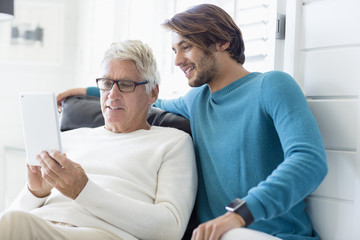 Happy father and son using digital tablet in living room