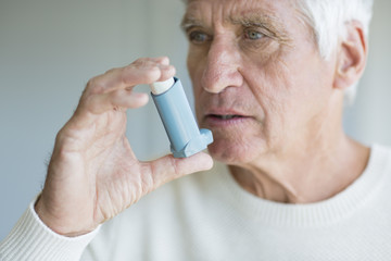 Close-up of a senior man using inhaler