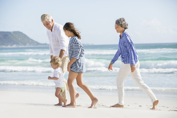 Old couple walking on the beach with their grand children