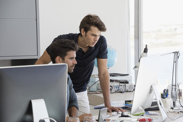 Two business executives working on computer in office