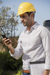 Male engineer using a mobile phone at site