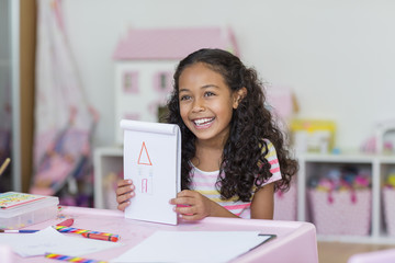Happy little girl showing her drawing