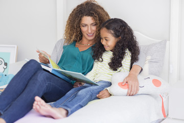Mother and daughter reading book on bed