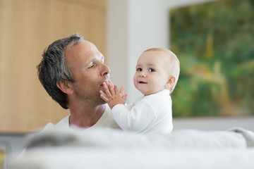 Father playing with his baby girl at home