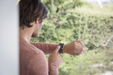 Young man using his smart watch