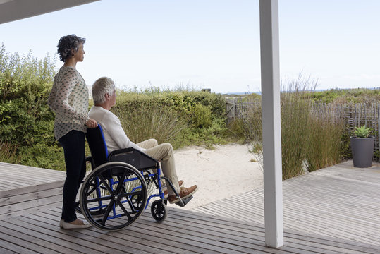 Senior man in wheelchair with his wife on porch