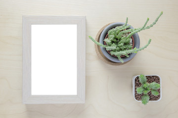Cactus in pot and blank photo frame on wooden table. Top view