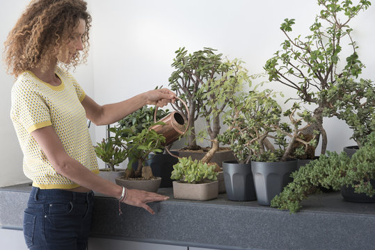 Side profile of a young woman watering potted plants
