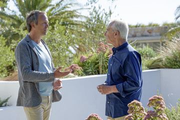Mature man talking with his elderly father in a garden