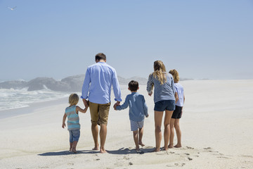 Rear view of a family of five walking on the beach