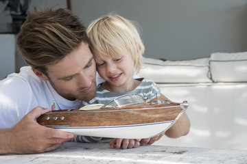 Happy father and son with a model boat