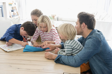Parents and children doing homework on table