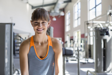 Portrait of a beautiful happy woman sitting on a exercise machine in a gym