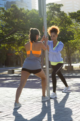 Young female athletes doing stretching exercise by pole on street