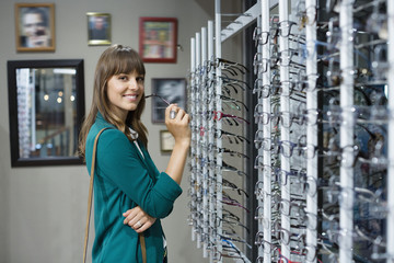 Happy young woman shopping for eyeglasses in optical shop