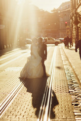 Sun rays hide the newlyweds standing on the tramways