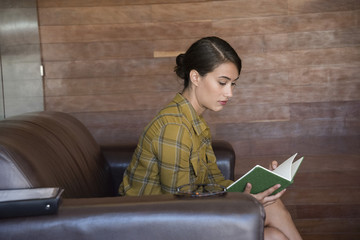 Businesswoman reading a book during office break