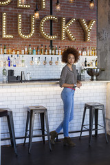 Portrait of a young woman standing at bar counter