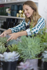 Happy woman arranging plants in her shop